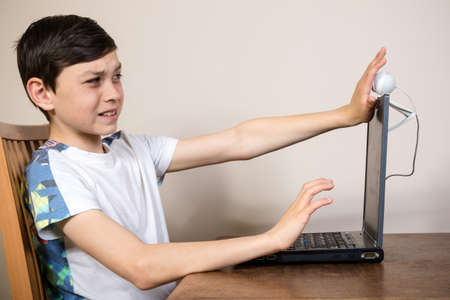 12 13: Young boy blocking a webcam