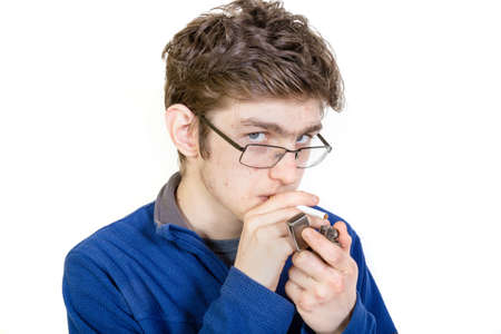 boy 15 year old: Teenage boy lighting a cigarette Stock Photo