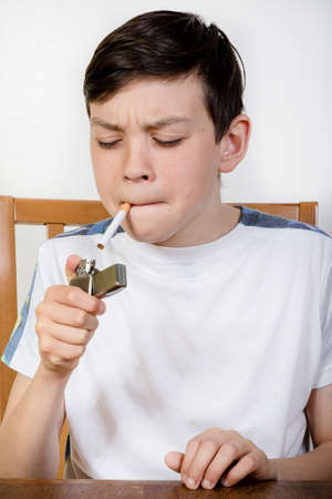 12 13: Young boy lighting a cigarette with a lighter