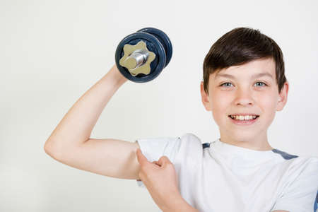 12 13: Happy young boy lifting a dumbbell, pointing at his bicep Stock Photo