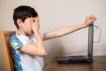 inappropriate: Young boy hiding his face from a web cam