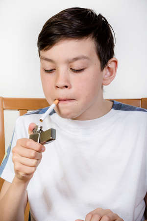 fag: Young boy lighting a cigarette with a lighter