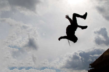 backflip: Teenage boy doing a back flip silhouetted