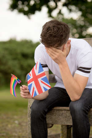 Depressed teenage boy with United Kingdom, Union Jack Flag and a Pride flag