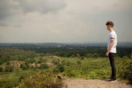 looking over: Teenage boy looking over landscape
