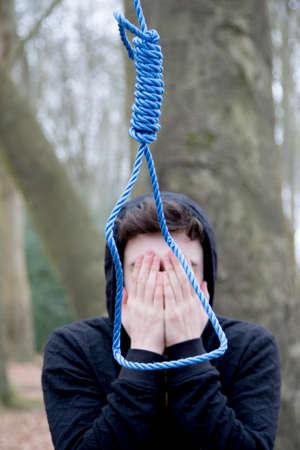 Depressed teenage boy with a hangmans noose