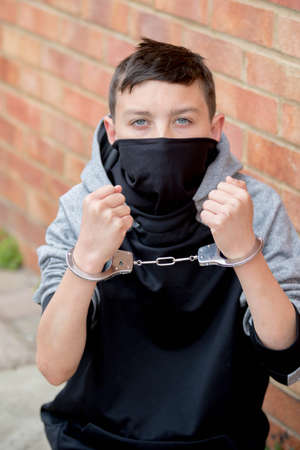 Young caucasian teenage boy in handcuffs after being arrested