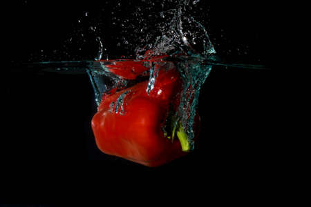 vegtables: Red Bell Sweet Pepper Droped Into Water Stock Photo