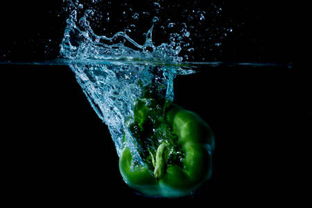 vegtables: Green Bell Sweet Pepper Droped Into Water