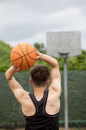 outside shooting: Teenage boy shooting a hoop on a basketball court Stock Photo