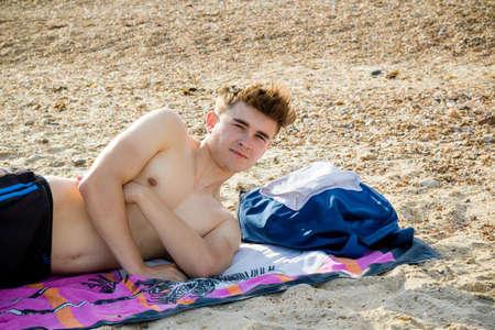 stoney: Teenage boy laying on a stoney beach