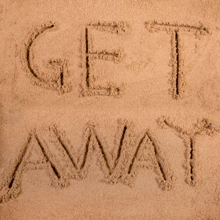 Get away written in soft wet sand on a beach 版權商用圖片