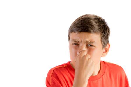 Jonge tiener die op een witte achtergrond wordt geïsoleerd die zijn neus houdt