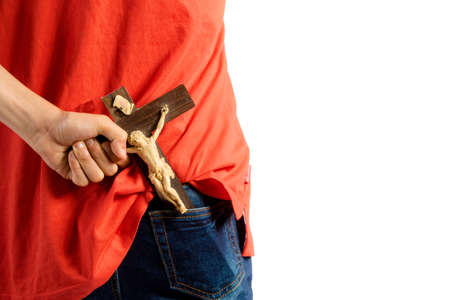Young teenage boy isolated against white removing a crucifix from his back pocket