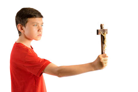 Young teenage boy isolated against white holding a cruxifix Stock Photo