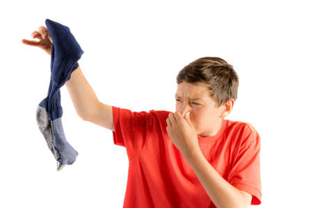 Young teenage boy isolated on a white background holding a smelly sock Stock Photo