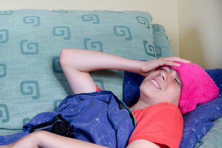 Unwell young teenage boy wrapped in a duvet on a sofa Stock Photo