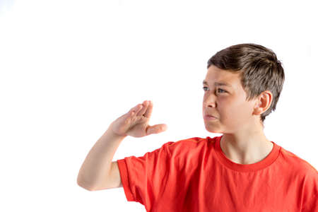 Young teenage boy isolated on a white background wafting a smell away Stock Photo
