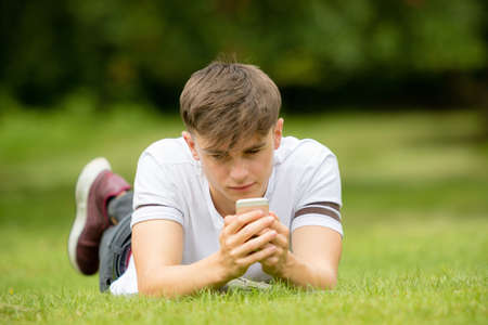 Teenage boy laying on grass on a summers day