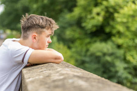 Teenage boy in a park on a warm summers day Stock Photo