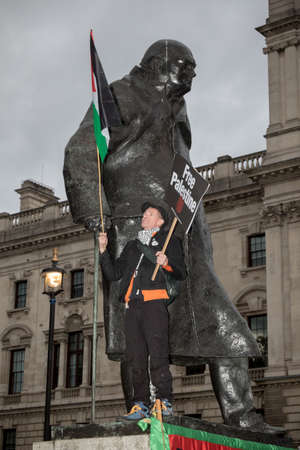 4th November 2017, London, United Kingdom:-Pro palestine protester stanind on the statue of Winston Churchil in parliment square Editorial