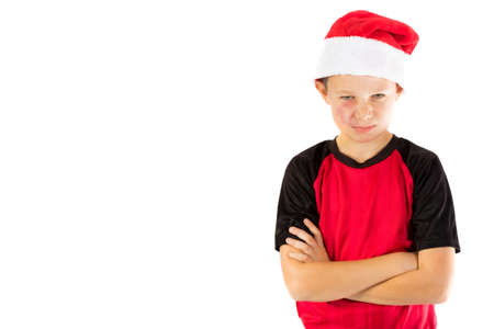 Pre-teen boy wearing a santa hat looking unhappy isolated on white Stock Photo