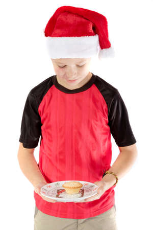 Pre-teen boy in christmas hat and a mince pie Stock Photo