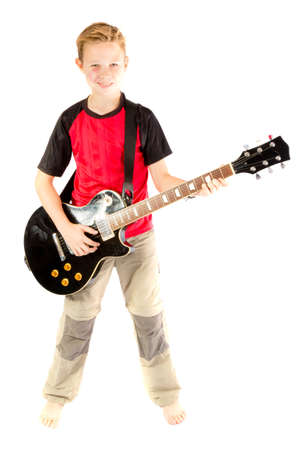 pre teen boy: Pre-teen boy and an electric guitar isolated on white background Stock Photo