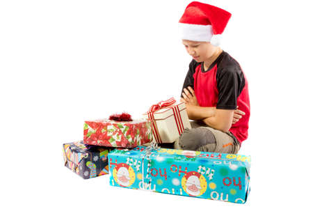 Sulking pre-teen boy with a pile of christmas gifts Stock Photo