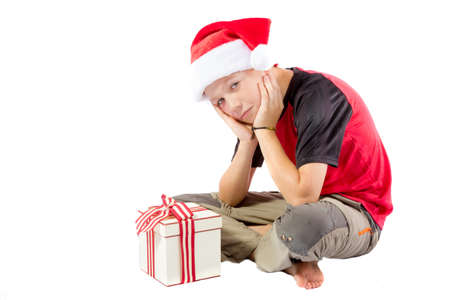 pre teen boy: Sulky pre-teen boy with a christmas gift isolated on white background Stock Photo