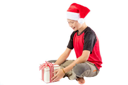pre teen boy: Happy pre-teen boy with a christmas gift isolated on white background