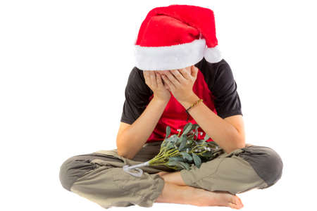 Sad pre-teen boy with mistletoe isolated on white background Stock Photo