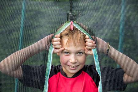 Cheeky pre-teen boy looking through trampoline net outside