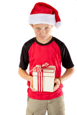Sulky pre-teen boy with a christmas gift isolated on white background Stock Photo