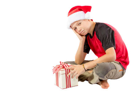 pre: Sulky pre-teen boy with a christmas gift isolated on white background Stock Photo