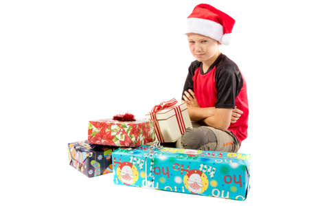 pre teen boy: Sulking pre-teen boy with a pile of christmas gifts Stock Photo