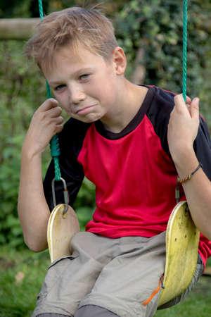 Sad pre-teen boy sitting on a swing outside