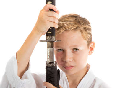 Pre-teen boy with a samurai sword isolated on a white background