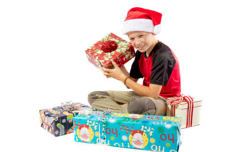 Happy pre-teen boy with a pile of christmas gifts isolated on white background