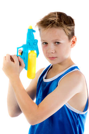 pre teen boy: Pre-teen boy playing with water pistols isolated on a white background