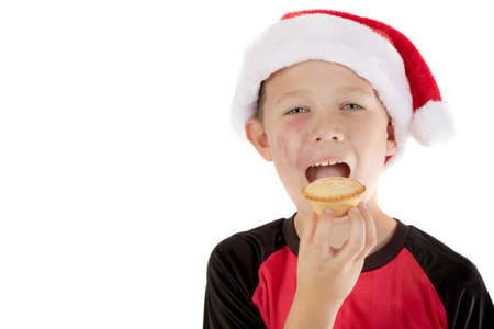 pre teen boy: Pre-teen boy in christmas hat and a mince pie Stock Photo
