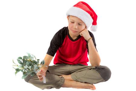 Sad pre-teen boy with mistletoe isolated on white background Stock Photo