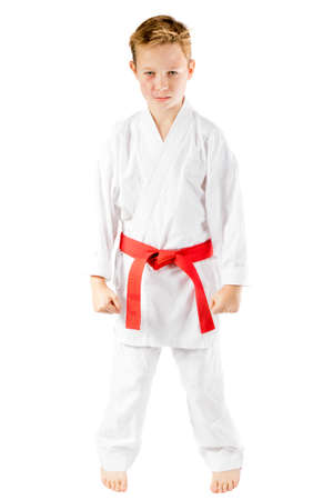 Pre-teen boy in martial arts uniform doing martial arts