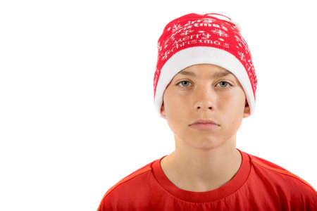 Sad caucasian teenage boy wearing a Christmas hat, isolated on white background Stock Photo