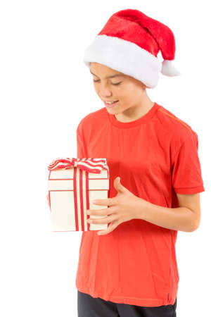 Young teenage boy looking at a Christmas gift, isolated on white background