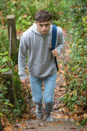 Teenage boy walking up concrete steps near a canal on an autumn day