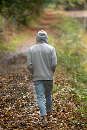 A young adult male walking alone outside on an autumn day Stock Photo