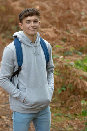 A portrait of a handsome eighteen year old boy in a wood on an autumn day Stock Photo