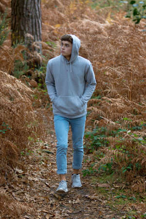 18 year old teenage boy walking in the woods on an autumn day