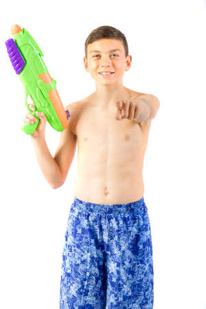 Young teenage boy playing with water guns isolated on a white background 免版税图像